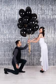 Photo de mariage. jeune couple avec des boules noires sur fond scintillant