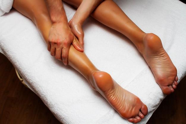 Photo de massage des jambes et des pieds. mains mâles d'un masseur.