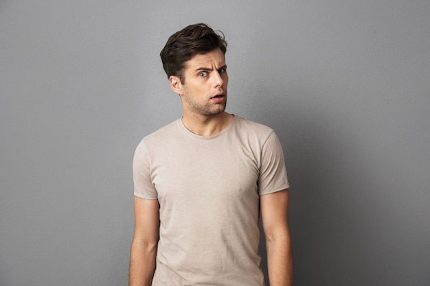 Photo d'un mec brune choquée ou perplexe regardant la caméra avec surprise