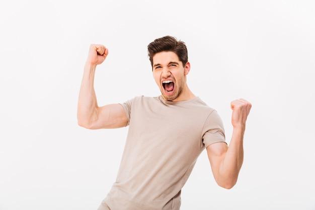 Photo d'un mec brunette heureux se réjouissant et serrant les poings comme un gagnant ou une personne chanceuse, isolé sur un mur blanc