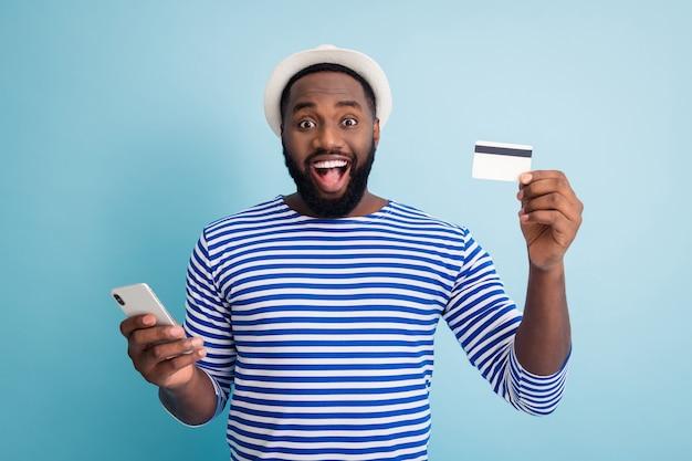 Photo de mec drôle de peau foncée tenir l'application de téléphone navigation faisant des achats en ligne utiliser une carte de crédit de service cool porter un chapeau de soleil blanc chemise de marin rayé mur de couleur bleu