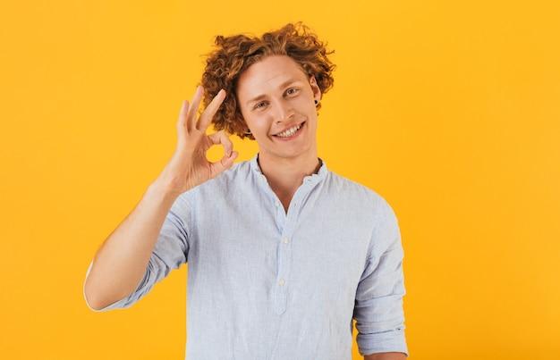 Photo de mec joyeux heureux souriant et montrant signe ok à la caméra, isolé sur fond jaune