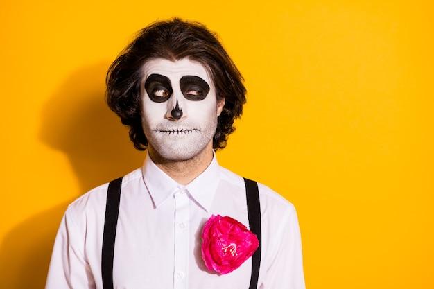 Photo d'un mec monstre zombie effrayant regarde l'espace vide rusé ludique préparer un tour intéressant les enfants portent une chemise blanche rose costume de mort bretelles isolé fond de couleur jaune