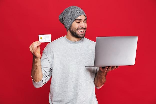 Photo d'un mec non rasé de 30 ans en tenue décontractée tenant une carte de crédit et un ordinateur portable en argent isolé