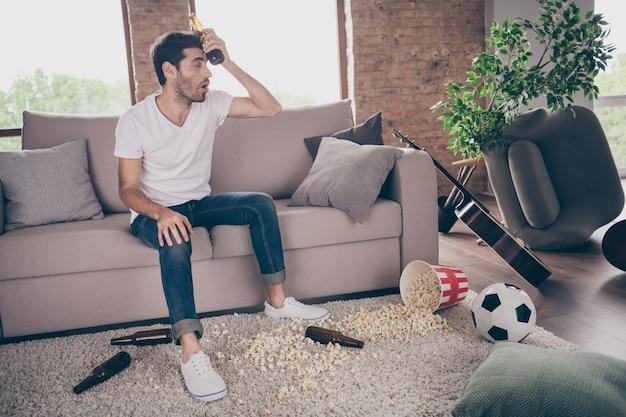 Photo d'un mec de race mixte assis sur un tapis appuyé sur un canapé tenir une bouteille de bière sur le front étage de pop-corn avait une fête de cerf fou souffrir de la gueule de bois matin mal de tête malpropre plat sale à l'intérieur