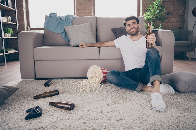 Photo de mec de race mixte assis tapis près de canapé tenant une bouteille de bière plancher de pop-corn s'amuser folle fête de cerf ne vous dérange pas sale plat sale réunion meilleurs amis invités à l'intérieur