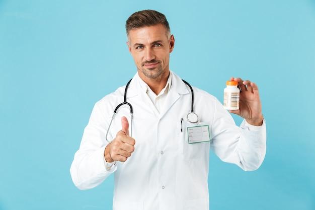 Photo d'un médecin de bel homme mûr posant isolé sur mur de mur bleu tenant des vitamines de pilules montrant les pouces vers le haut.