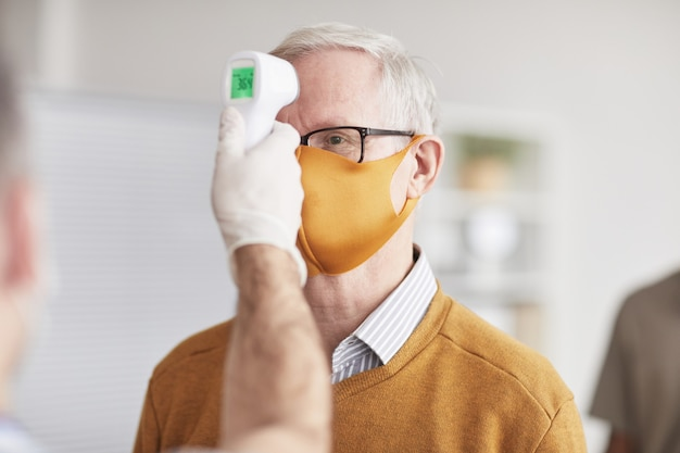 Photo d'un médecin méconnaissable vérifiant la température d'un homme âgé portant un masque en ligne à la clinique ou à l'hôpital, espace de copie