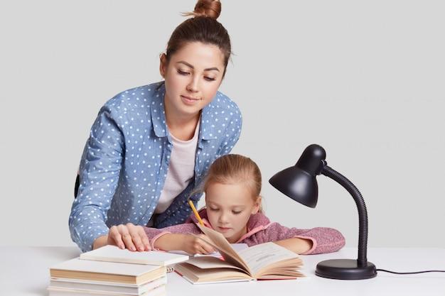 Photo de la mère et la fille posent ensemble sur le bureau, écrivent des informations dans le cahier, lisent de nombreux livres, se préparent pour les cours à l'école, participent à l'étude, isolées sur le mur du studio blanc