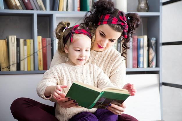 Photo de la mère et de la fille sont assises sur le sol et lisent