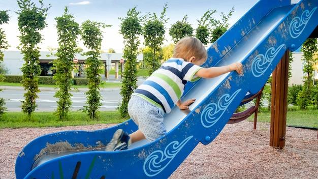Photo d'un mignon petit garçon de 3 ans grimpant et montant sur un grand toboggan sur une aire de jeux pour enfants au parc