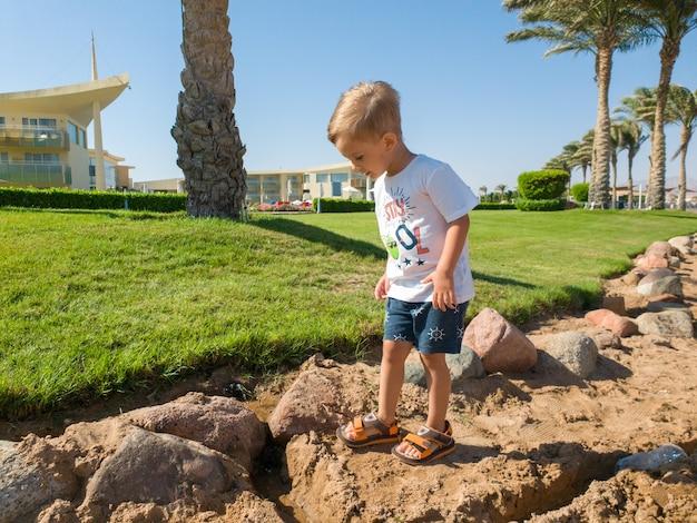 Photo d'un mignon petit garçon marchant à la mer avec des palmiers en croissance et une belle pelouse verte à l'hôtel