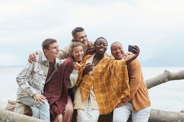 Photo minimale d'un groupe diversifié de jeunes prenant un selfie sur la plage dans l'espace de copie d'automne