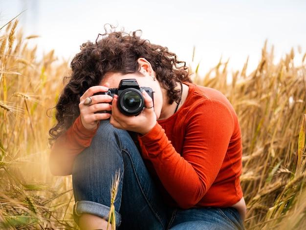 Photo de mise au point peu profonde d'une belle jeune femme prenant une photo avec son appareil photo