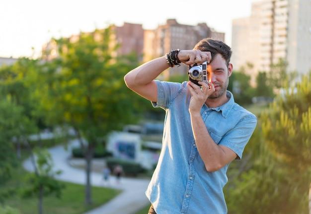 Photo de mise au point peu profonde d'un jeune homme prenant une photo dans le parc