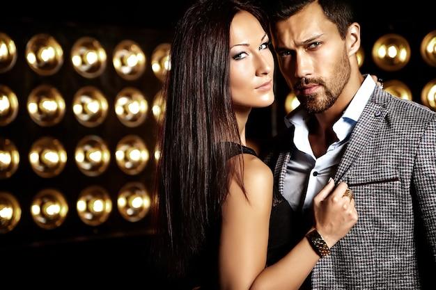 Photo de mode de bel homme élégant en costume avec une belle femme sexy posant sur fond de lumières de studio noir