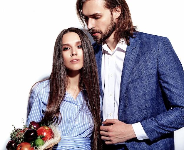 Photo de mode de bel homme élégant en costume avec une belle femme sexy en robe colorée sur blanc