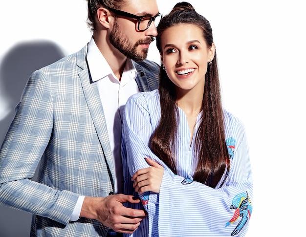 Photo de mode de bel homme élégant dans des verres en costume avec une belle femme sexy en robe colorée sur blanc
