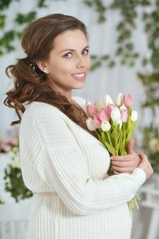 Photo de mode d'une belle femme enceinte aux longs cheveux noirs posant à l'intérieur du studio avec des tulipes
