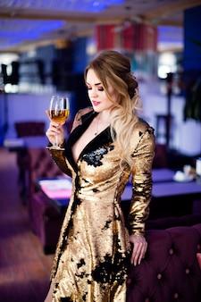 Photo de mode de la belle femme sensuelle aux cheveux bouclés dans des vêtements élégants au café, boire de la vigne