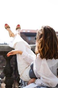 Photo de mode d'une belle fille se reposant sur le balcon