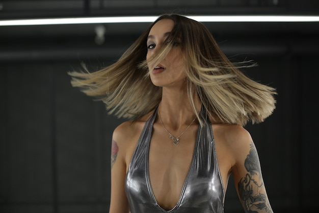 Photo de mode d'une belle fille sensuelle aux cheveux blonds dans un luxueux body argenté posant à l'intérieur mode prise de vue photo de haute qualité
