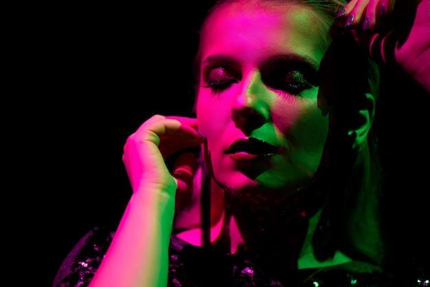 Photo de mode d'une fille sexy vêtue de noir dans la discothèque.
