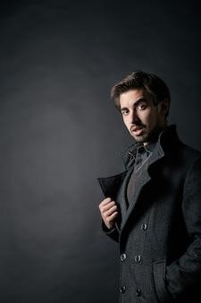 Photo de mode d'un jeune bel homme en manteau sur fond noir