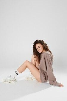 Photo de mode d'une jeune femme modèle avec de longues jambes parfaites portant un sweat-shirt gris de longues chaussettes blanches et des baskets tendance isolées sur le mur blanc avec espace de copie