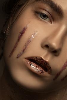 Photo de mode de jeune fille blonde beauté blonde avec un maquillage élégant avec des larmes de paillettes. maquillage, portrait en gros plan en vue couleur. dodge et burn et décomposition de fréquence.