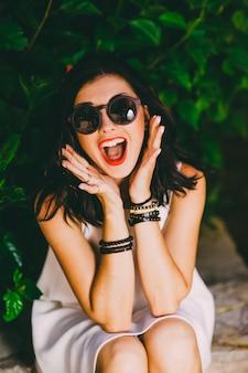 Photo de mode en plein air de belle femme sensuelle avec des cheveux noirs en robe blanche luxueuse