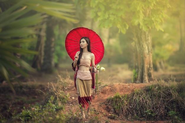 Photo de mode en plein air de la belle jeune femme dans un paysage d'automne avec des fleurs sèches.