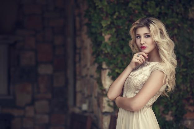 Photo de mode en plein air d'une élégante belle femme aux cheveux blonds en robe de paillettes luxueuse, posant dans le parc d'été