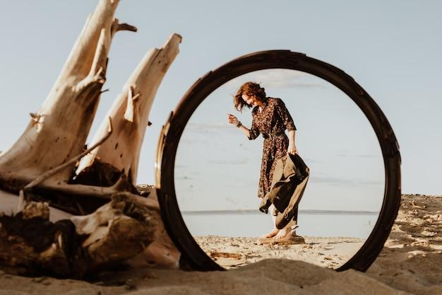 Photo de mode de vie atmosphérique en plein air de belle jeune femme aux cheveux noirs en robe et veste marchant sur la plage dans le reflet du miroir.