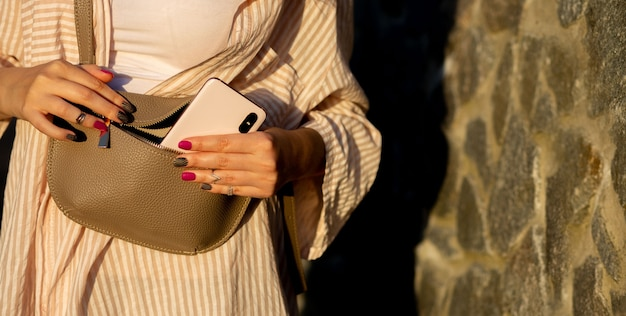 Photo de mode de vie d'une jeune femme habillée décontractée sortant le téléphone du sac à main. espace libre