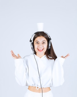 Photo d'un modèle de jeune fille heureuse avec un casque tenant une tasse au-dessus.
