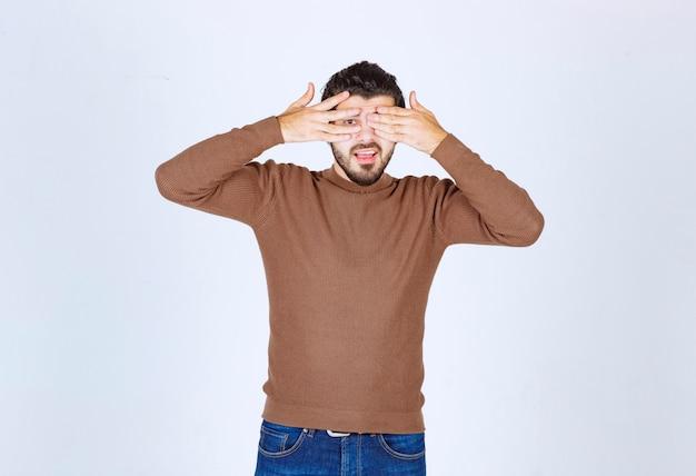 Photo d'un modèle de jeune homme debout et couvrant ses yeux. photo de haute qualité