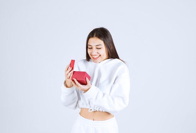 Photo d'un modèle de jolie jeune fille tenant une boîte-cadeau.