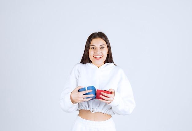 Photo d'un modèle de jolie jeune fille tenant des coffrets cadeaux.