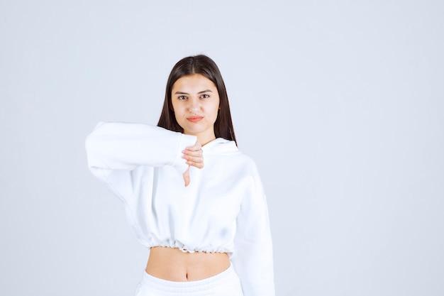 Photo d'un modèle sérieux de jeune fille montrant un pouce vers le bas.