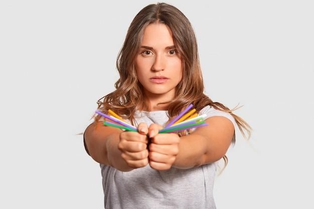 Photo de modèles féminins sûrs d'elle porte des pailles colorées en plastique dans les deux mains, regarde directement la caméra, contre la pollution plastique, vêtu d'un t-shirt décontracté isolé sur le mur du studio blanc