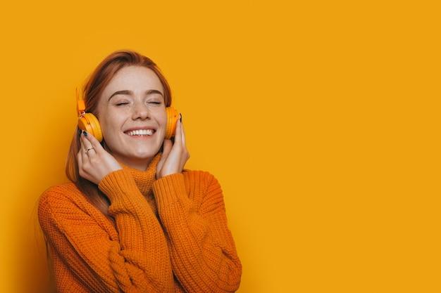 Photo monochrome d'une dame de race blanche aux cheveux roux et taches de rousseur, écouter de la musique à l'aide d'un casque