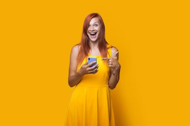 Photo monochrome d'une femme de race blanche avec une robe et des cheveux rouges pointant vers son téléphone sur un mur de studio jaune