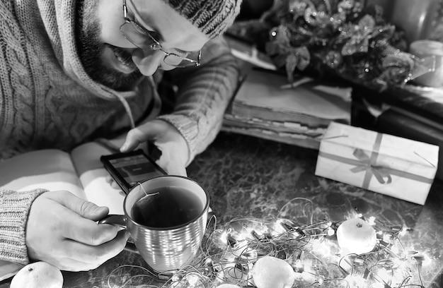 Photo monochrome d'un homme avec un livre blanc dans les mains pour la table du nouvel an avec des décorations
