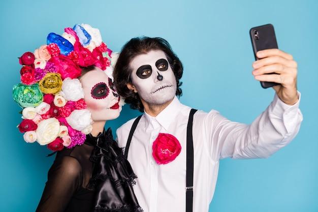 Photo de monstre effrayant deux personnes homme dame câlin tenir téléphone faire selfie anniversaire éternel porter robe noire costume de mort roses bandeau bretelles isolé fond de couleur bleu
