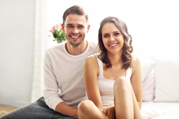Photo montrant un couple heureux assis sur le lit en vêtements de nuit