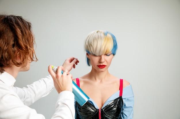 Photo montrant une femme adulte au salon de coiffure. photo de studio de jeune fille gracieuse avec coupe courte élégante et cheveux colorés sur fond gris et mains de coiffeur.