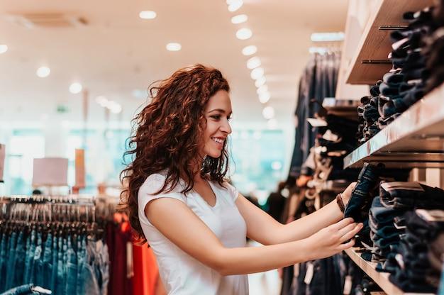 Photo montrant une femme heureuse faisant des emplettes pour des vêtements.