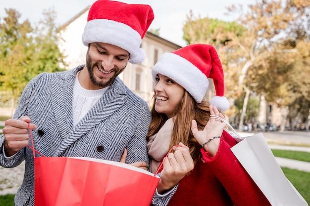 Photo montrant un jeune couple faisant des achats de noël dans la ville