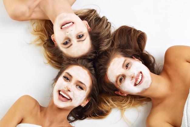 Photo montrant trois amis avec des masques faciaux sur fond blanc